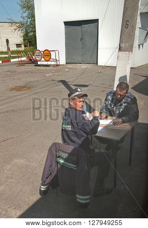 Chernobyl, Ukraine - May 9, 2011: Police officers check papers at the checkpoint in Chernobyl Exclusion Zone, place of Chernobyl nuclear disaster. Every year on May 9 people, evacuated from Exclusion Zone, are allowed to visit their homes.