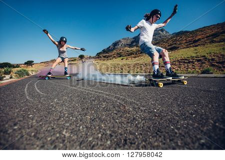 Young People Longboarding Down The Road