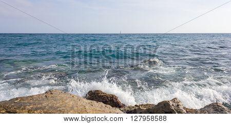 Panoramic of sea waves crashing against rocks.