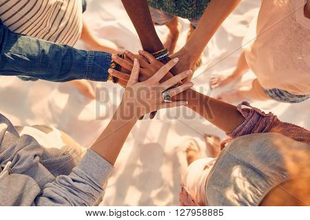 Hands Of Young People On Stack At Beach