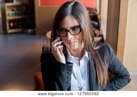 Young woman in glasses talking on the phone in a cafe and looks upset. She frowns and unhappy