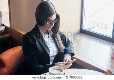 Beautiful girl sits in a cafe drinking coffee and writing in my phone notes