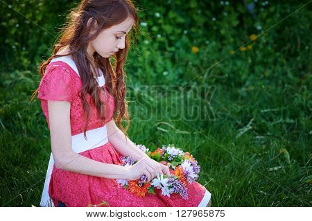 beautiful woman weaves a wreath on the grass.