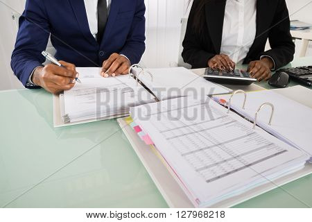 Close-up Of Two Businesspeople Calculating Invoice With Calculator At Desk
