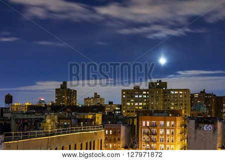 New York City rooftop skyline view at night with moon rising above