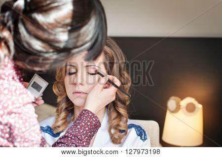 bride is doing make up for wedding celebration.