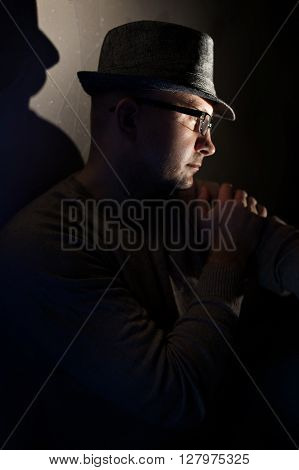 Studio photo of young attractive man wearing glasses and hat.
