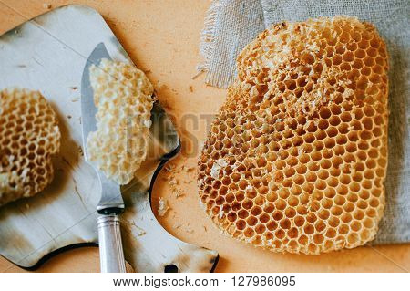 Hollow honeycomb pieces on wooden plate with knife