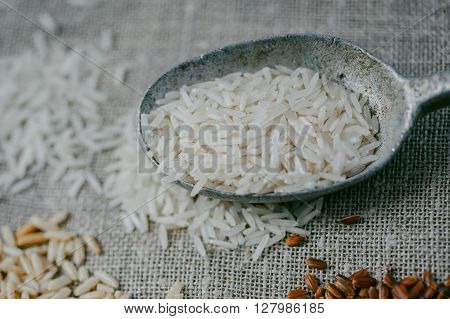 Raw white rice in old silver spoon on burlap background
