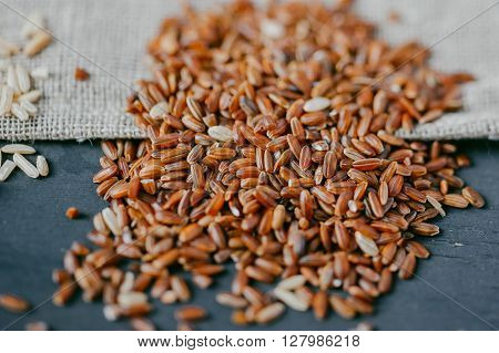 Heap of red Rice on black wooden background with burlap sack ** Note: Shallow depth of field