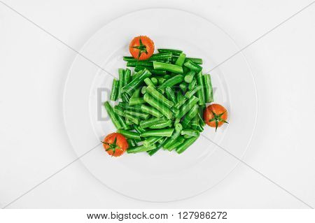 Cooked asparagus with fresh cherry tomatoes isolated on white plate
