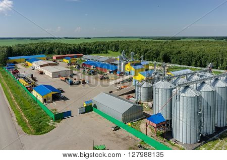 Novikova, Russia - June 18, 2015: Aerial view onto modern machine yard of agricultural firm Russian Field. Corn dryer silos standing in machine yard. Tyumen region