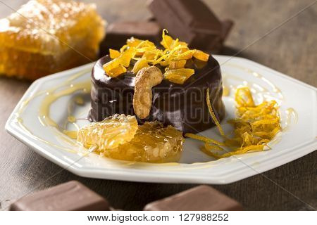 Lebkuchen With Pieces Of Apricot Above It In A Plate And Chocolates And A Piece Of Honeycomb Over A