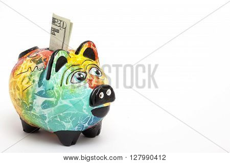Saving dollars in a Colorful piggy bank -  side view