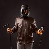 welder in protective helmet with welding apparatus in the hands on brown background poster