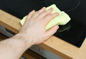 Man's hand wipes cooktop in the kitchen. poster