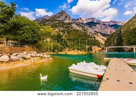 White catamarans and geese swim in azure water. Boat mooring on the Verdon River. The picturesque Verdon Gorge. Concept of ecological and active tourism
