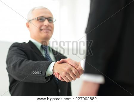 closeup of a business handshake partners. the image is blurred.