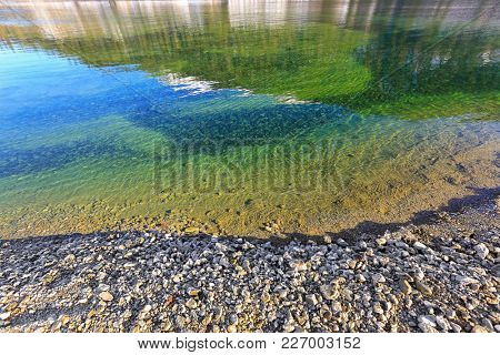 Frosted stone on lakeside with fresh blue green Turquoise lake water, winter in Tyrol, Austria, Europe