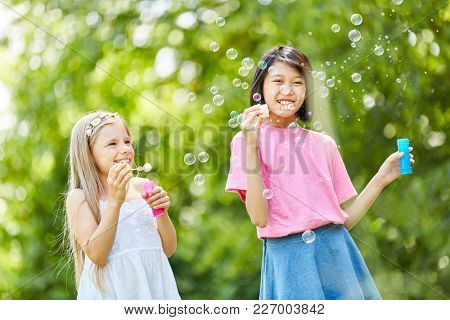 Two girls are happy about the floating soap bubbles in nature