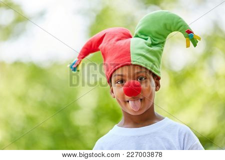 African boy disguised as harlequin with fool cap shows the tongue