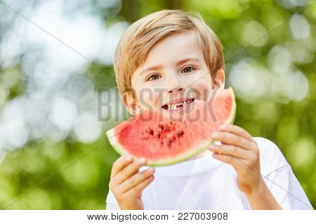 Hungry boy at a party is eating a delicious and healthy watermelon