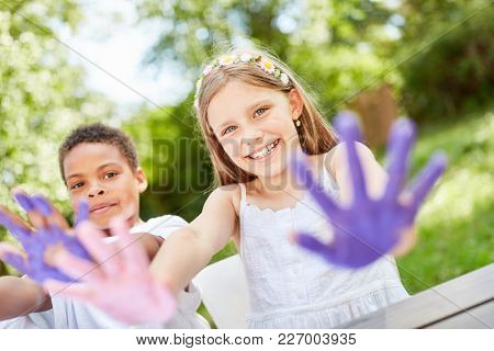 Children play and paint with finger paints on birthday party in the garden