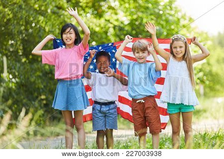 Multicultural group of kids with the USA flag is waving happily