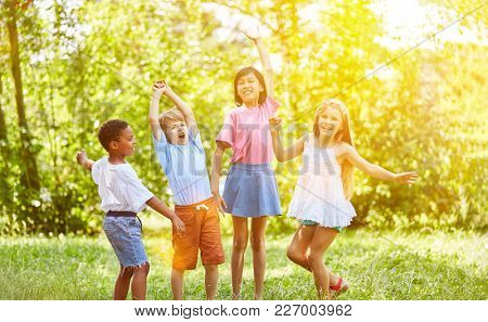 Group of kids cheering and dancing in summer in the park