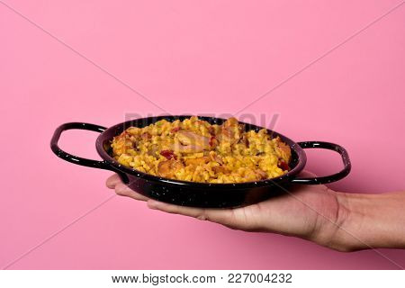 closeup of a young caucasian man holding a typical spanish paella valenciana in a typical paella pan, against a pink background with some blank space on top