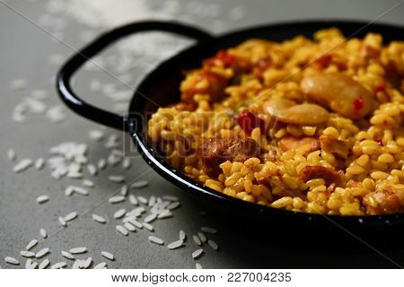 closeup of a typical spanish paella valenciana in a typical paella pan, on a gray rustic surface