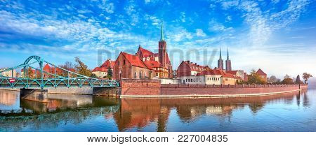 Wroclaw Poland view at Tumski island and Cathedral of St John the Baptist with bridge through river Odra. Picturesque landscape autumn day blue sky white cloud.