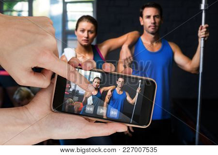 Portrait of fit serious friends in gym against hands touching smart phone