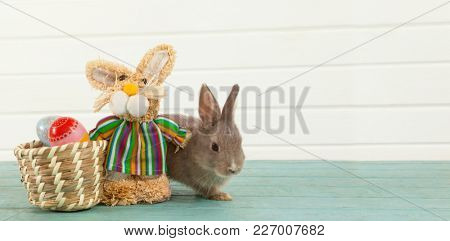 Easter eggs on wicker basket with Easter bunny and toy against wooden background