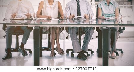 Group of business people sitting at table in office