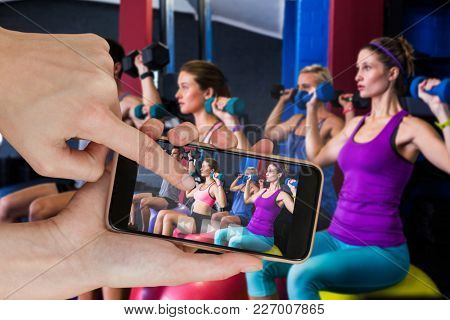 Friends holding dumbbells while sitting on fitness ball against hands touching smart phone