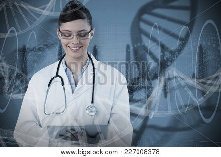 Beautiful female doctor using digital tablet against blue spiral dna pattern on screen