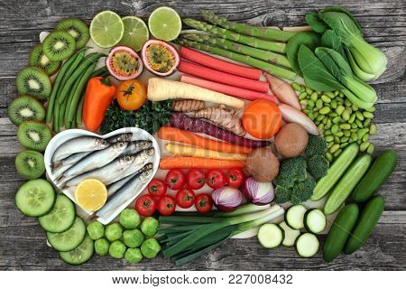 Health food for healthy eating concept with fresh vegetables and fruit top view. Health food high in antioxidants, anthocyanins, minerals, vitamins and fibre.