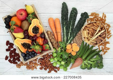 Health food high in fibre with whole wheat pasta, nuts, fruit and vegetables with super foods high in antioxidants, omega 3 fatty acids, anthocyanins and vitamins. Rustic background, top view.