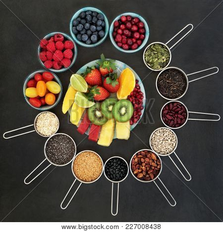 Health and super food concept to promote fitness and a healthy heart with fruit, vegetables, nuts, seeds, grains and pulses. Foods high in omega 3, anthocyanins, antioxidants and smart carbohydrates.