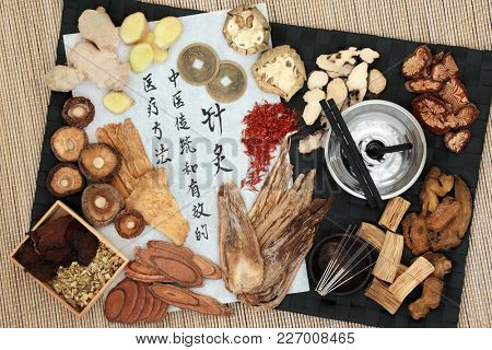 Chinese moxa sticks and acupuncture needles with herbs, feng shui coins and calligraphy script. Translation reads as acupuncture chinese traditional and effective medical treatment solution.