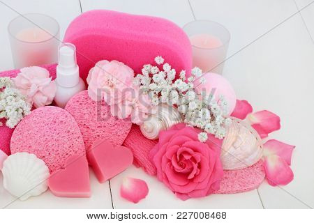 Spa and bathroom beauty treatment accessories with pink rose and carnation flowers, heart shaped soaps, body lotion, bath bomb, sponges, wash cloth, ex foliating scrub with decorative seashells.