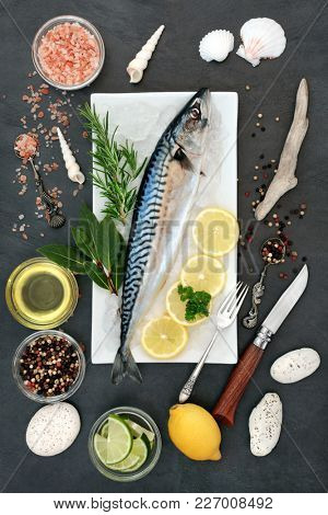 Mackerel fresh fish health food on crushed ice with herbs, peppercorns, olive oil, himalayan salt, lemon and lime on slate background. High in omega 3 and beneficial for a healthy heart.