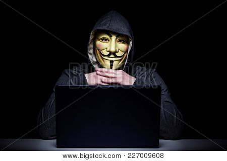 MILAN,ITALY, February, 2018: Hacker wear anonymus mask with notebook in the dark