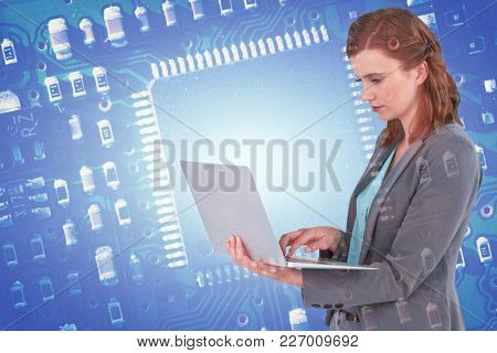 Businesswoman typing on laptop computer against blue micro electronic circuit