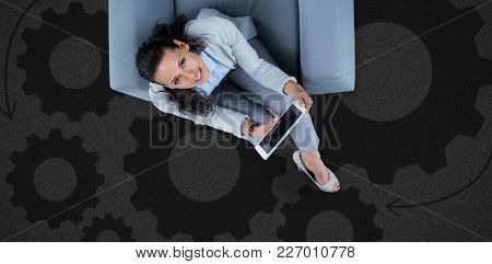 Woman on her tablet looking up against black background