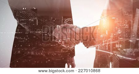 High angle view of illuminated cityscape against composite image of business people shaking hands