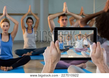 Cropped hand holding digital tablet against instructor taking yoga class