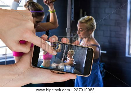 Female trainer instructing woman in gym against hands touching smart phone