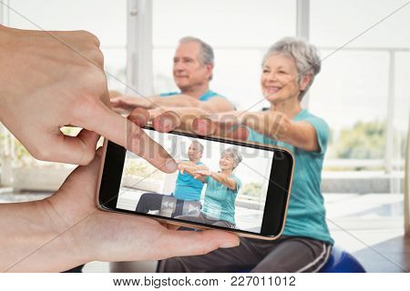 Hands touching smart phone against happy senior couple performing exercise